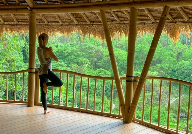 Lady doing a yoga pose overlooking the forest